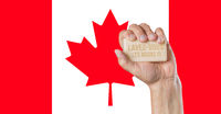 Caucasian male hand holding soap with words: Lavez-vous les mains, in French against a Canadian flag background