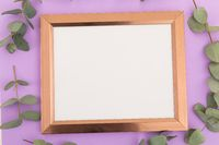 Wooden frame with white background surrounded by green leaves on purple