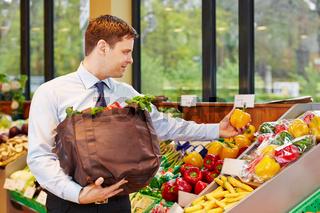 Geschäftsmann kauft Gemüse im Biomarkt