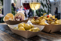 Tapas bar. Olives, potato chips, cheese and jamon, red and white wine, on a wooden table in an outdoors cafe