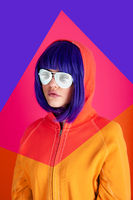 Art collage with alternative funky girl with blue hair on bright blue purple pink background. Close up fashion portrait young beautiful woman in hoodie and white glasses. Unusual youth fashion concept