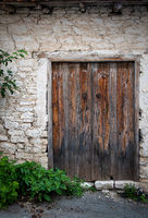 Entrance gate of an abandoned house with a  closed vintage wooden door