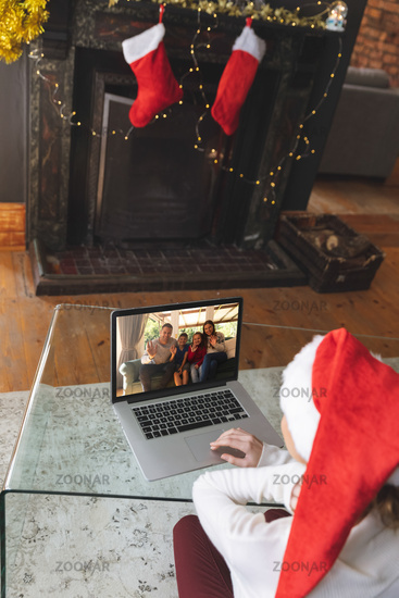 Rear view of woman in santa hat having a videocall with family in santa hats waving on laptop at hom