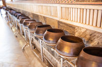 View of row of many bronze bowls standing on long stand