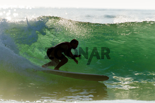 Long boarder surfing the waves at sunset