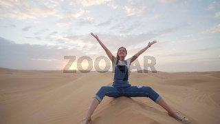 A happy girl in the desert of the Arab Emirates throws up sand.