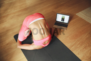 Woman doing morning yoga in the home, using laptop cor yoga online.