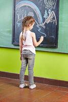 Mädchen zeichnet mit Kreide an Tafel
