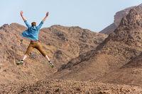 Freudiger junger Mann springt in der Wüste