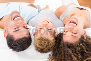 Laughing young family lying on bed together