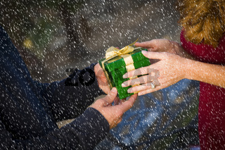 Hands of Man and Woman Exchanging Christmas Gift in Snow