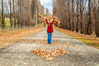 Woman throwing leaves in air in front of heart of fallen leaves Autumn