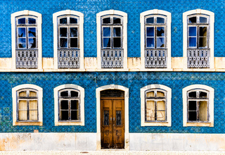 A frontal view of a house facade covered in azulejo tiles with broken windows and wooden door