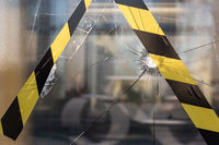 Barrier tape and a broken window in the city