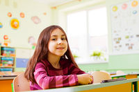 Happy smiling girl sitting in her class
