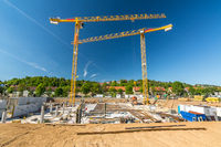 Construction site with large excavation and cranes on a sunny day