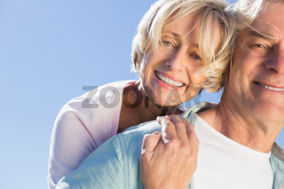 Happy senior man giving his partner a piggy back