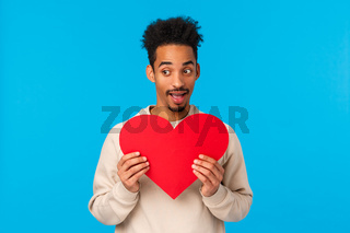 Excited and happy african american guy in love, confess his feelings during valentines day date, holding cute heart sign over chest and looking away shy as express affection, stand blue background