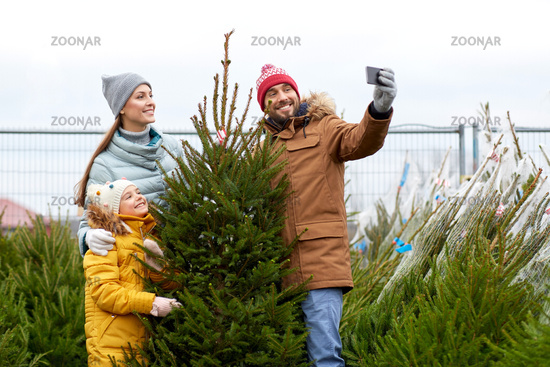 family taking selfie with christmas tree at market