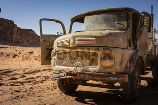 old rusty and worn-out broken vintage truck standing in the desert. Bullet holes in the windscreen. Abandoned vehicle.