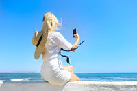 Unrecognizable blond woman taking selfie near sea