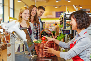 Frau bezahlt Gemüse an der Kasse im Supermarkt