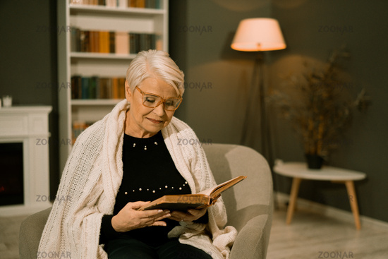Wise Senior Woman In Eyeglasses Reads Old Book
