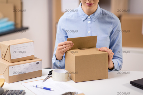 woman packing parcel box at post office