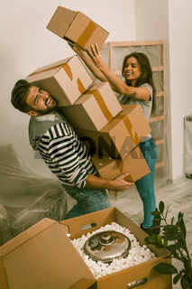 Young man and woman relocating to new apartment unpacking boxes