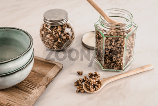 Homemade healthy and nutritious keto diet breakfast granola in  glass jars with wooden spoons and blue ceramic bowls on marble kitchen table in fresh morning light