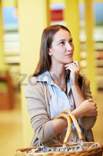 Nachdenkliche Frau im Supermarkt