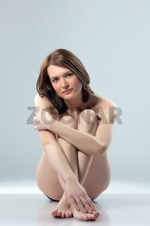 Studio shot of cute young brunette posing naked