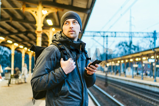 Sopot Fast Urban Railway station. young man standing and waiting train on platform. tourist travels by train. Portrait Of Caucasian Male In Railway Train Station. traveler with backpack waiting train