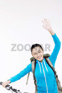 Young woman with backpack,taking a bike