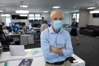 Portrait of senior businessman wearing face mask with arms crossed at modern office