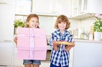 Kinder mit Geschenk und Kuchen am Geburtstag