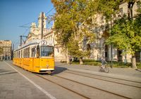 Yellow tram moving along city road in Budapest, Hungary.