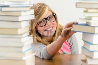 Smiling student girl take book from stack
