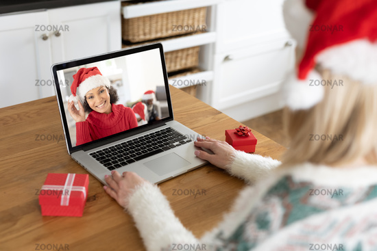 Woman in Santa hat having a video chat with another woman on her laptop at home
