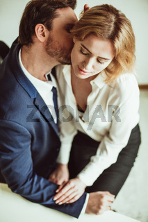 Love affair at work. Business man kisses neck of a woman sitting on his lap. Two people flirting together in office. High angle view