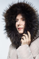 Portrait of a young female in a winter coat with fur trimmed hood.
