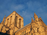 side view of the central tower of york minster in sunlight against a blue cloudy sky