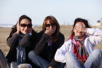 three girls in three stances blind, mute and deaf on the beach