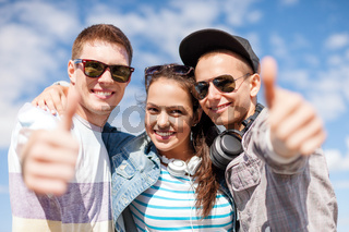 smiling teenagers showing thumbs up
