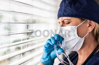 Stressed Female Doctor or Nurse On Break At Window Wearing Medical Face Mask and Goggles