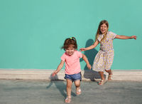 Cheerful little sisters in colorful dresses runing against green wall