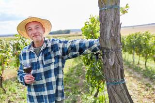 Weinbauer mit Glas Rotwein im Weinberg