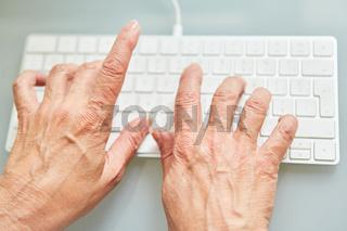 Hände von Senior schreiben auf PC Tastatur