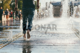 The middle plan of the bare feet of a man in jeans who runs between the streams of the city fountain