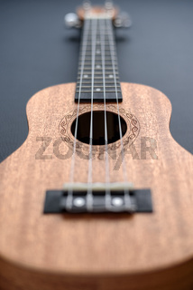 Brown ukulele on black background with shallow depht of field